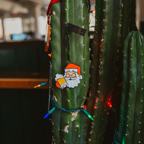 Santa beer ornament hanging from a cactus