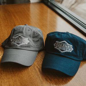 Both Diamond Logo Dad Cap next to each other on table