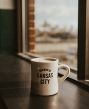 Load image into Gallery viewer, Brewed in KC Mug side with coffee