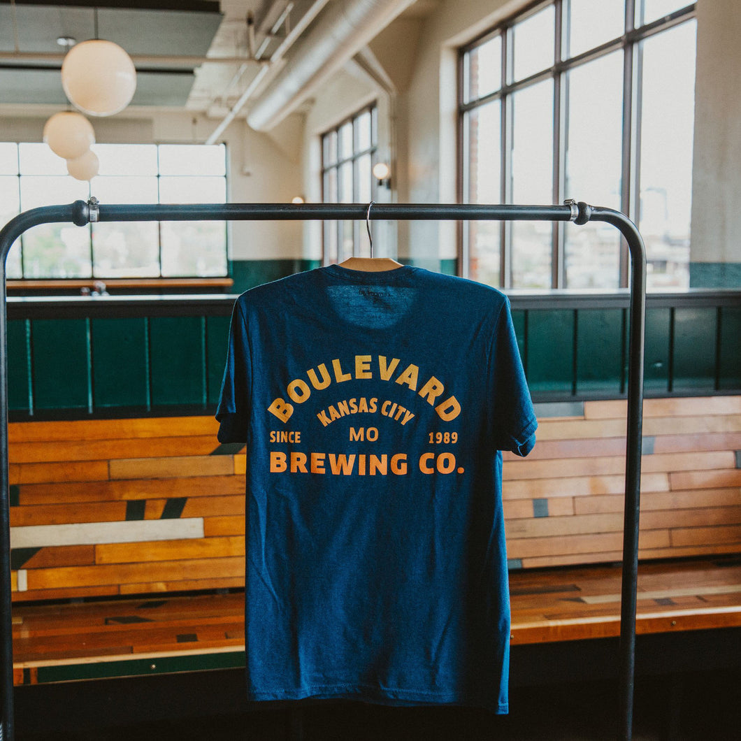 Backside of navy t-shirt with Boulevard Brewing Co. arch logo printed in a yellow to orange gradient