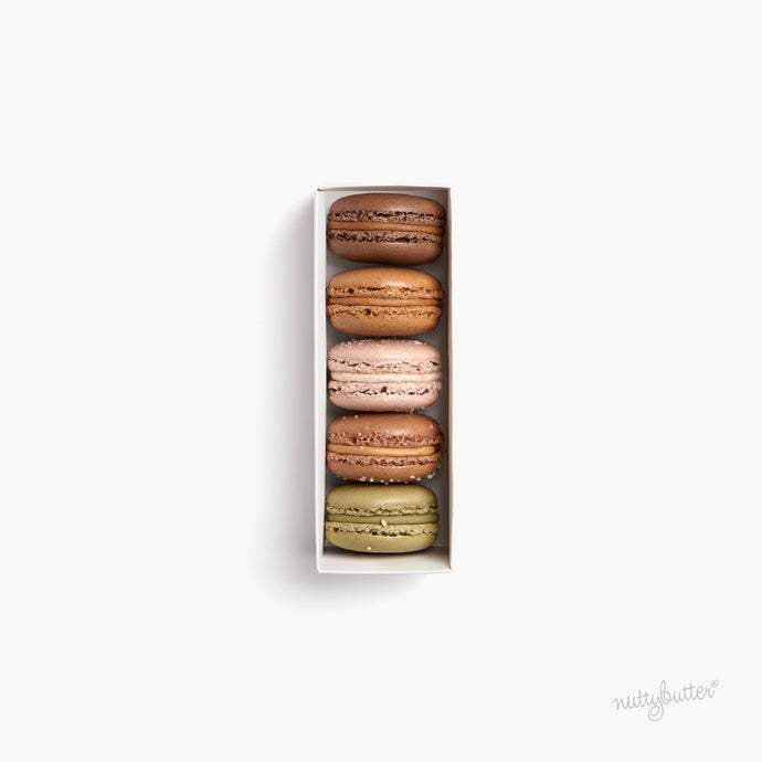 Nuttybutter box of 5 french macarons. This macaron gift box includes Nuttybutter's Sicilian pistachio macaron, coconut cashew macaron, Sicilian hazelnut macaron, dark cacao macaron and sea salt caramel macaron.