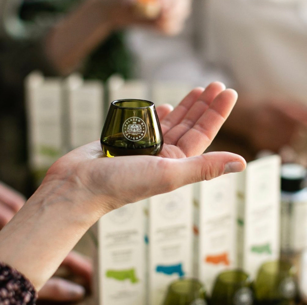 Person holding green extra virgin olive oil tasting cup with Palazzo di Varignana logo in the palm of their hand with a background of different extra virgin olive oils