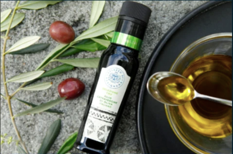 One of the extra virgin olive oil blends next to an olive branch, tomatoes, and a bowl with oil