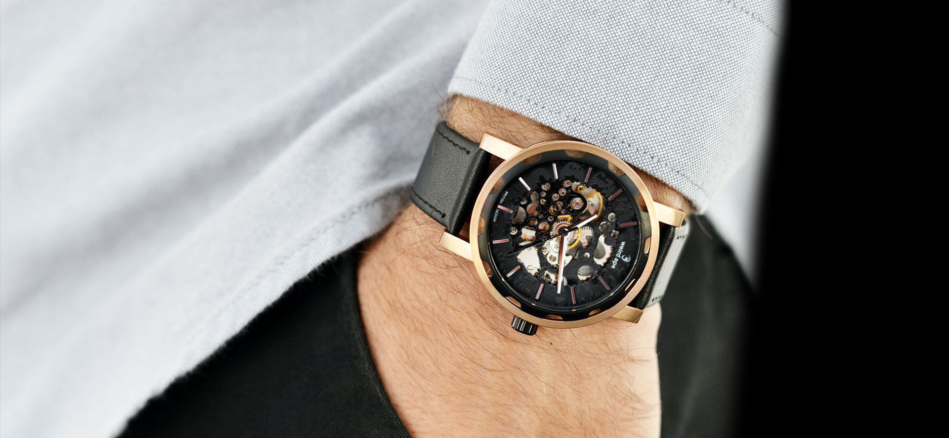 Rose Gold skeleton watch with black strap in a lifestyle image