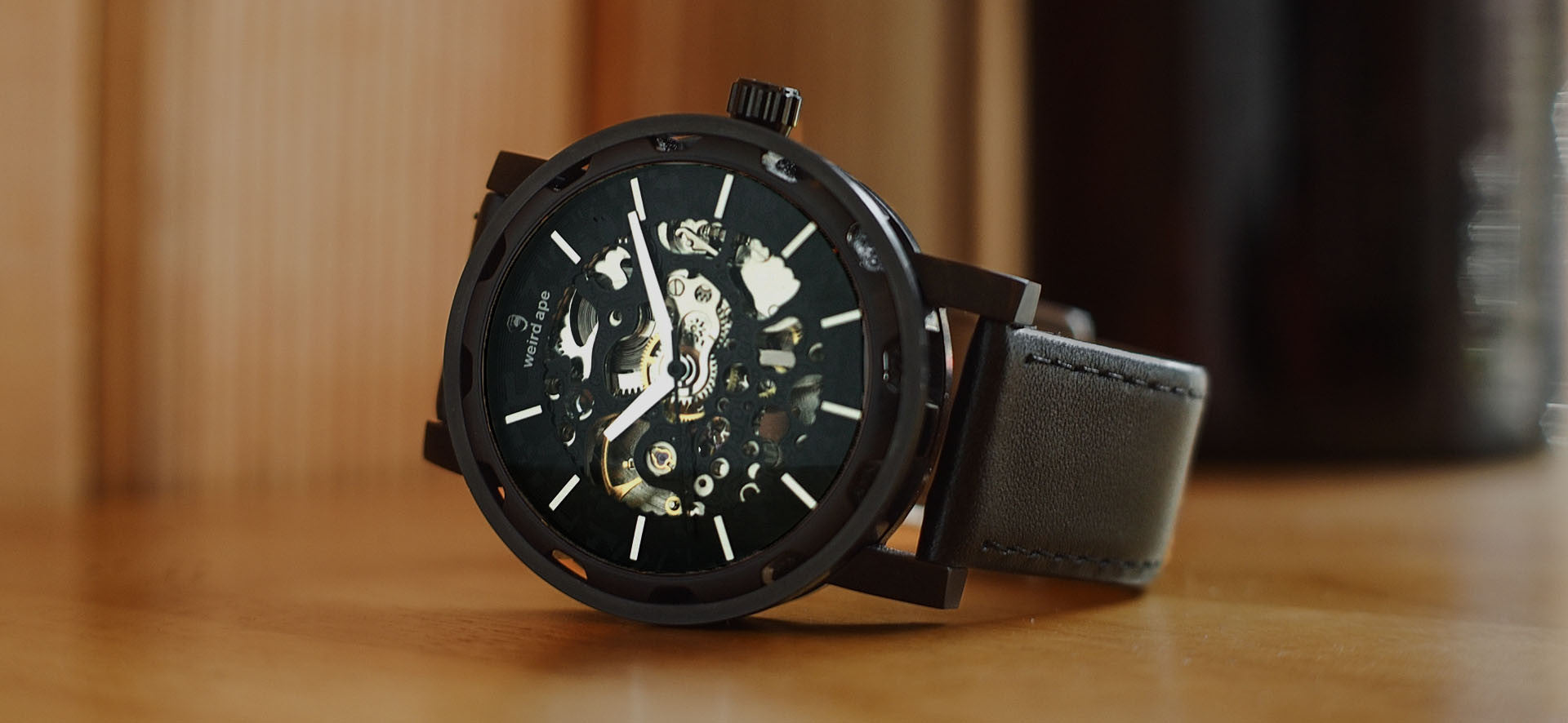 Black skeleton watch with leather black strap in a lifestyle image