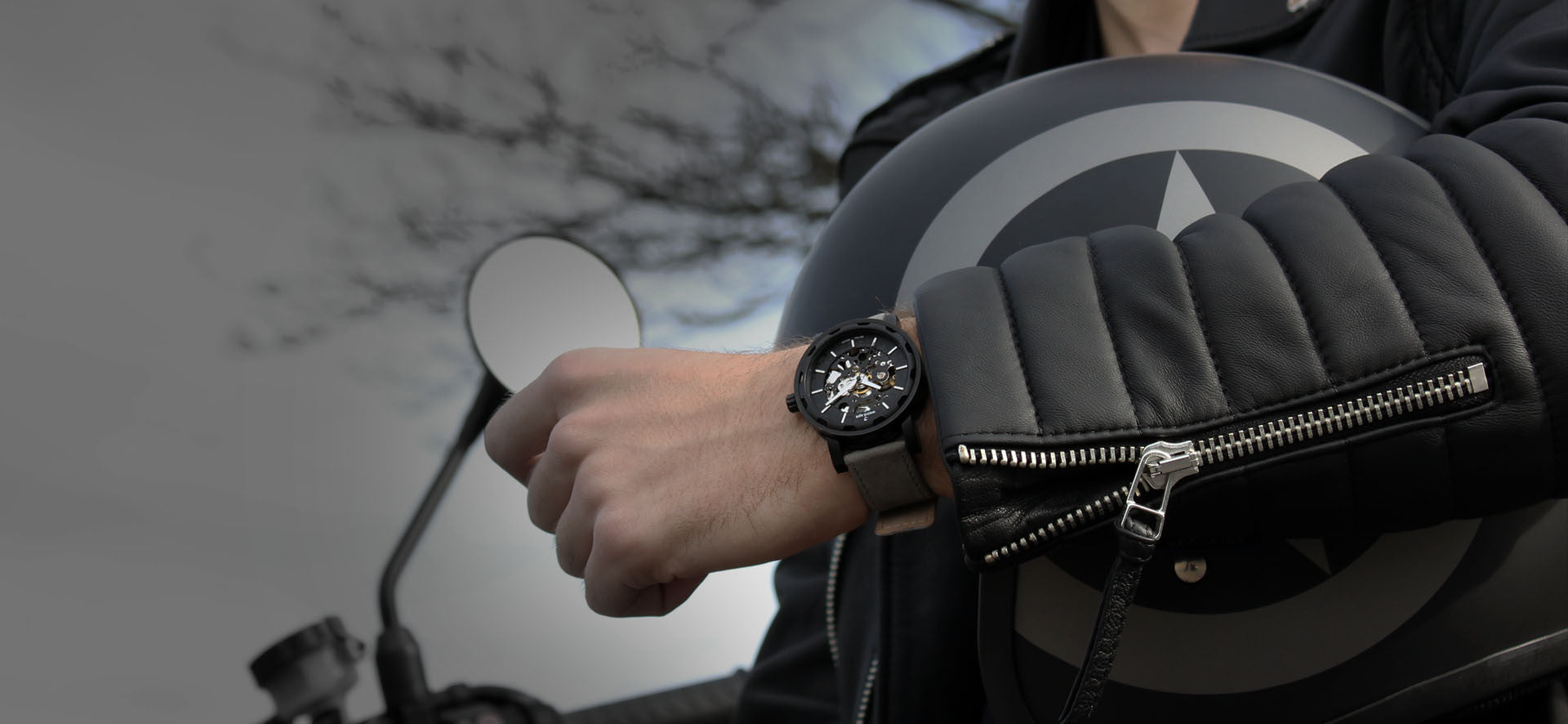 Black skeleton watch with a grey strap in a lifestyle image