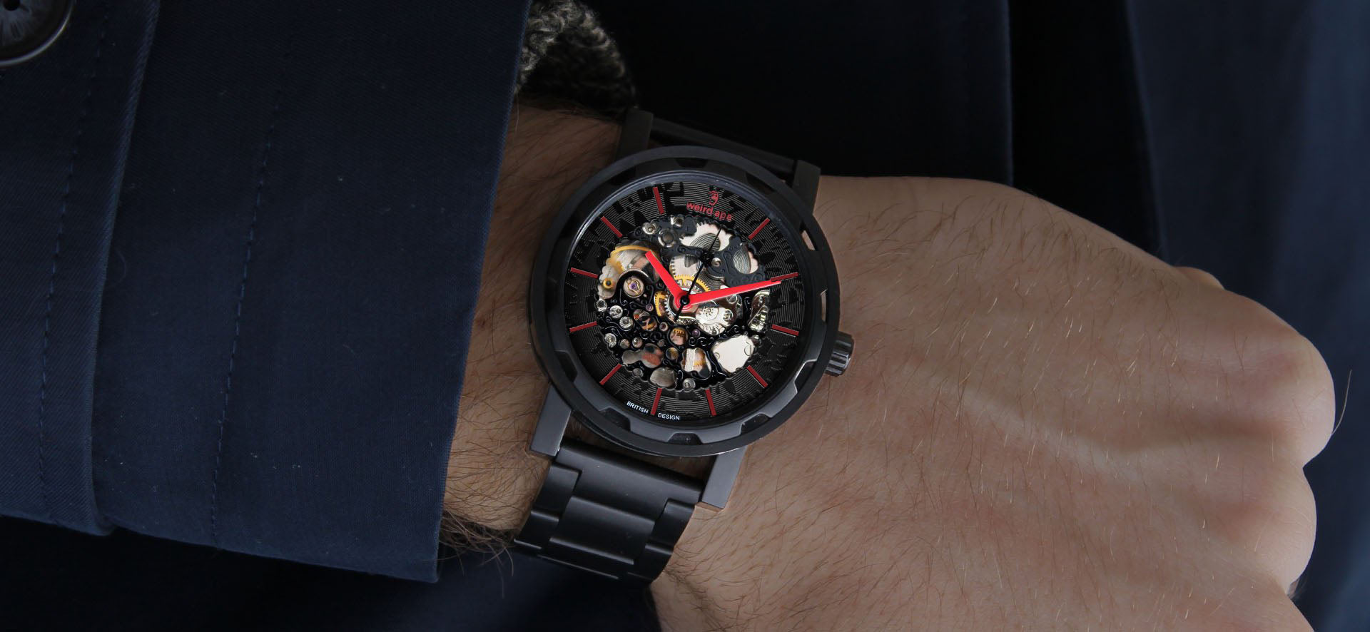 Black skeleton watch with red hands and a metal strap in a lifestyle image
