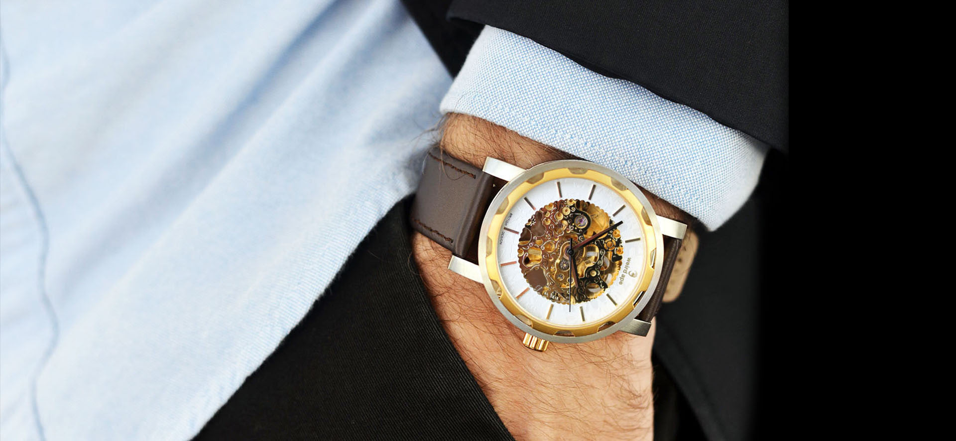 Gold skeleton watch with a brown strap in a lifestyle image
