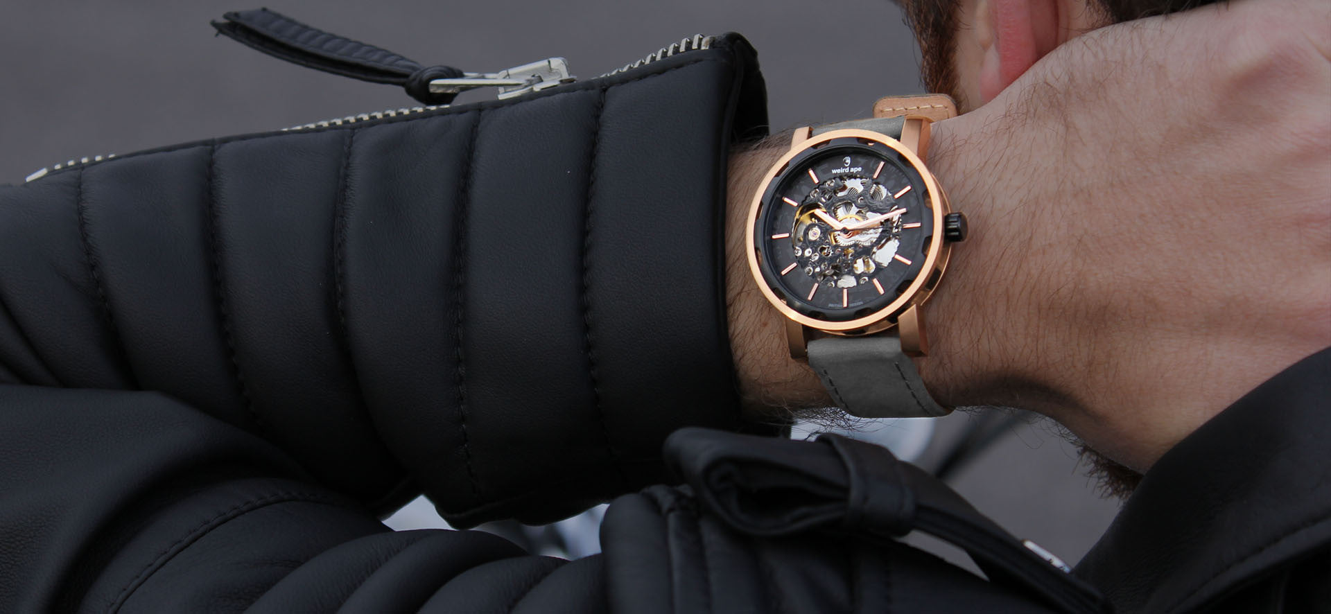 Rose gold skeleton watch with a grey strap in a lifestyle image