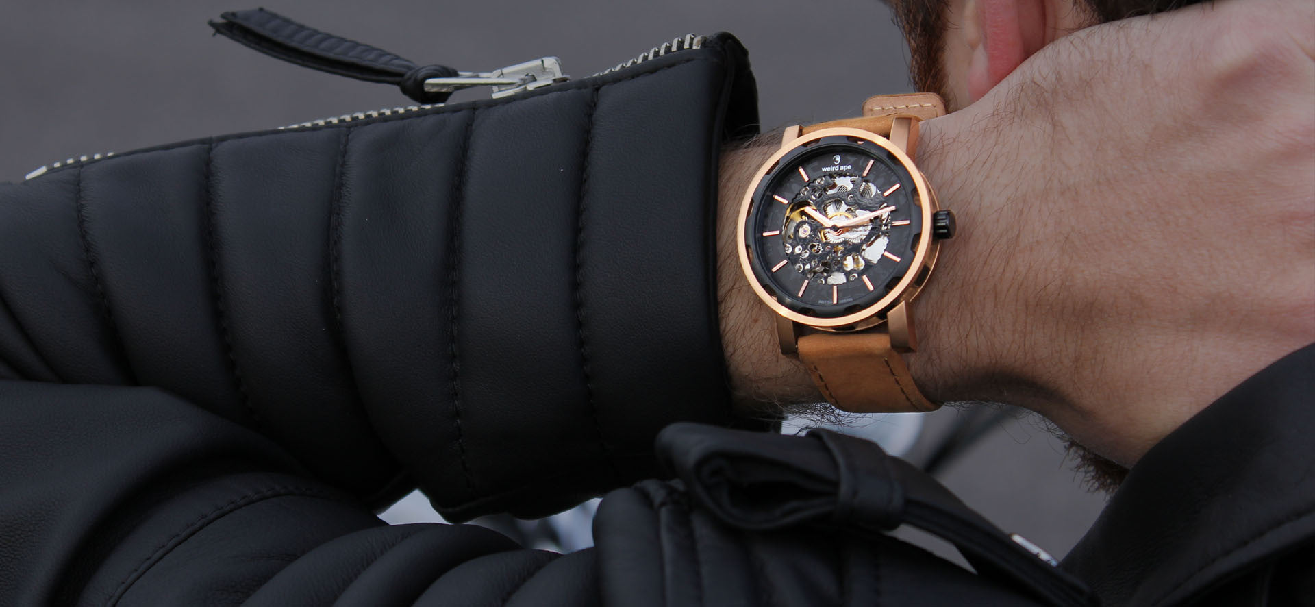 Rose gold skeleton watch with a tan strap in a lifestyle image