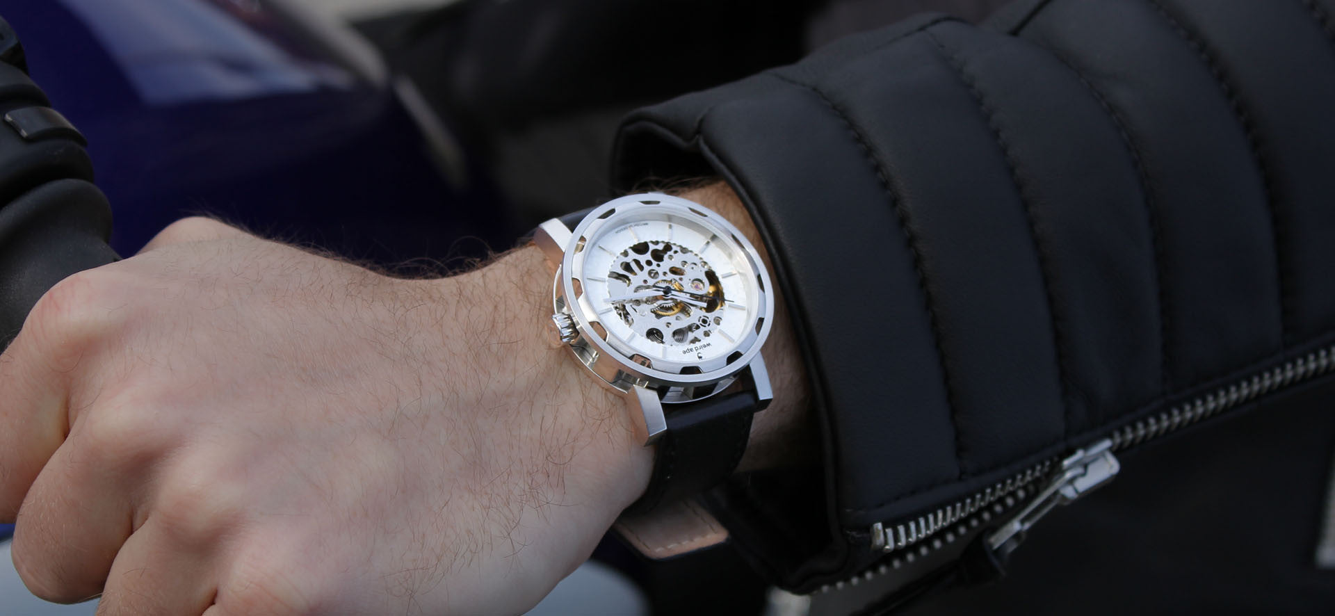Silver skeleton watch with a black strap in a lifestyle image