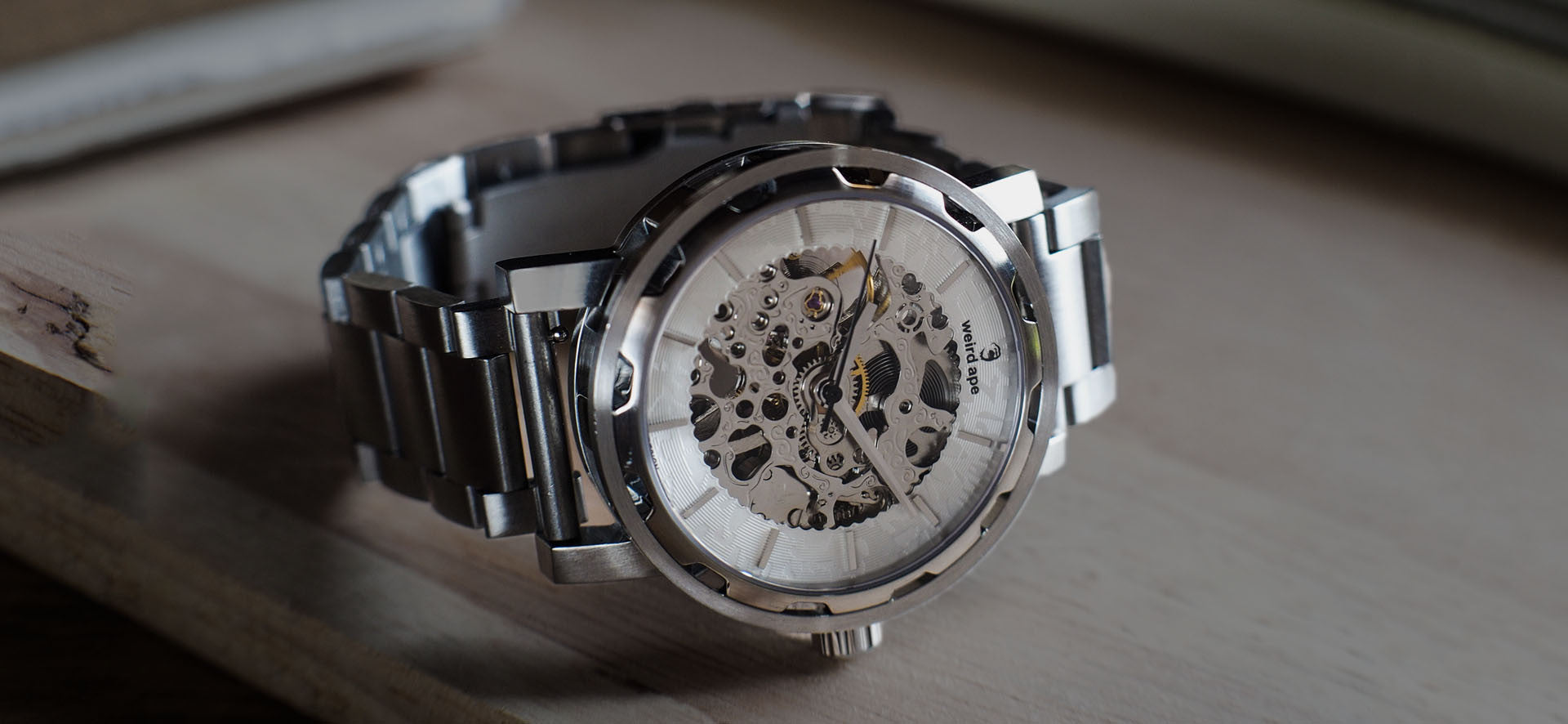 Silver skeleton watch with a silver strap in a lifestyle image