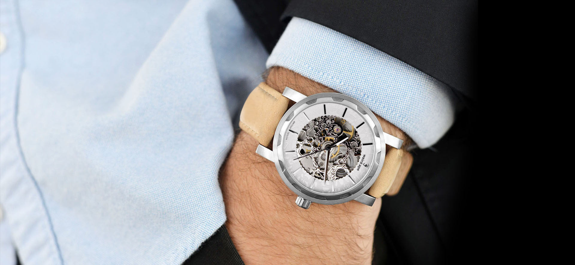 Silver skeleton watch with a sandstone strap in a lifestyle image