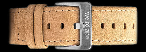 A sandstone suede leather strap with silver buckle for a mechanical watch.