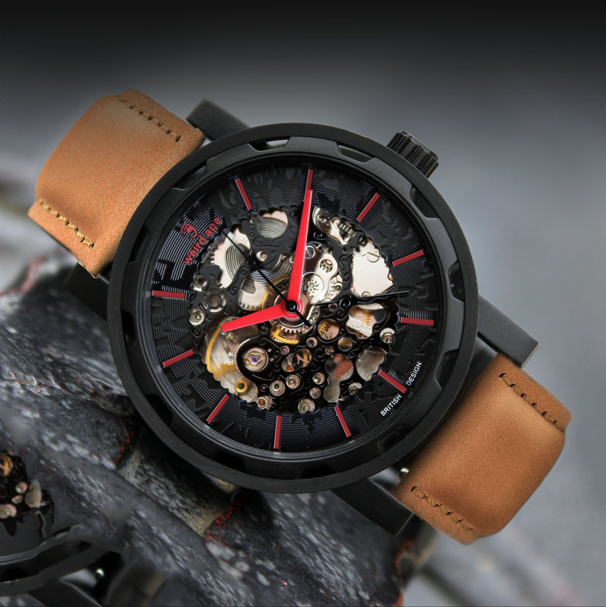 A picture of a black mechanical watch with a tan leather strap.