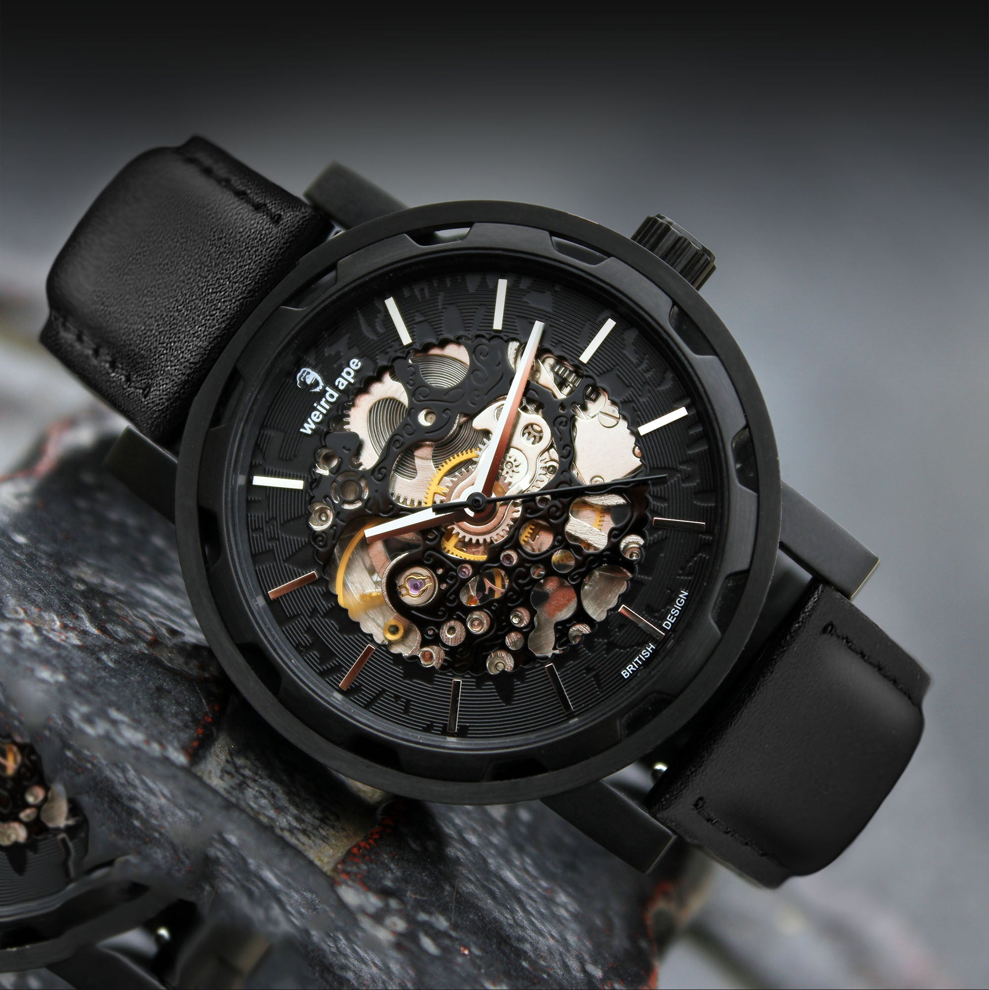 A picture of a black mechanical watch with a black leather strap.