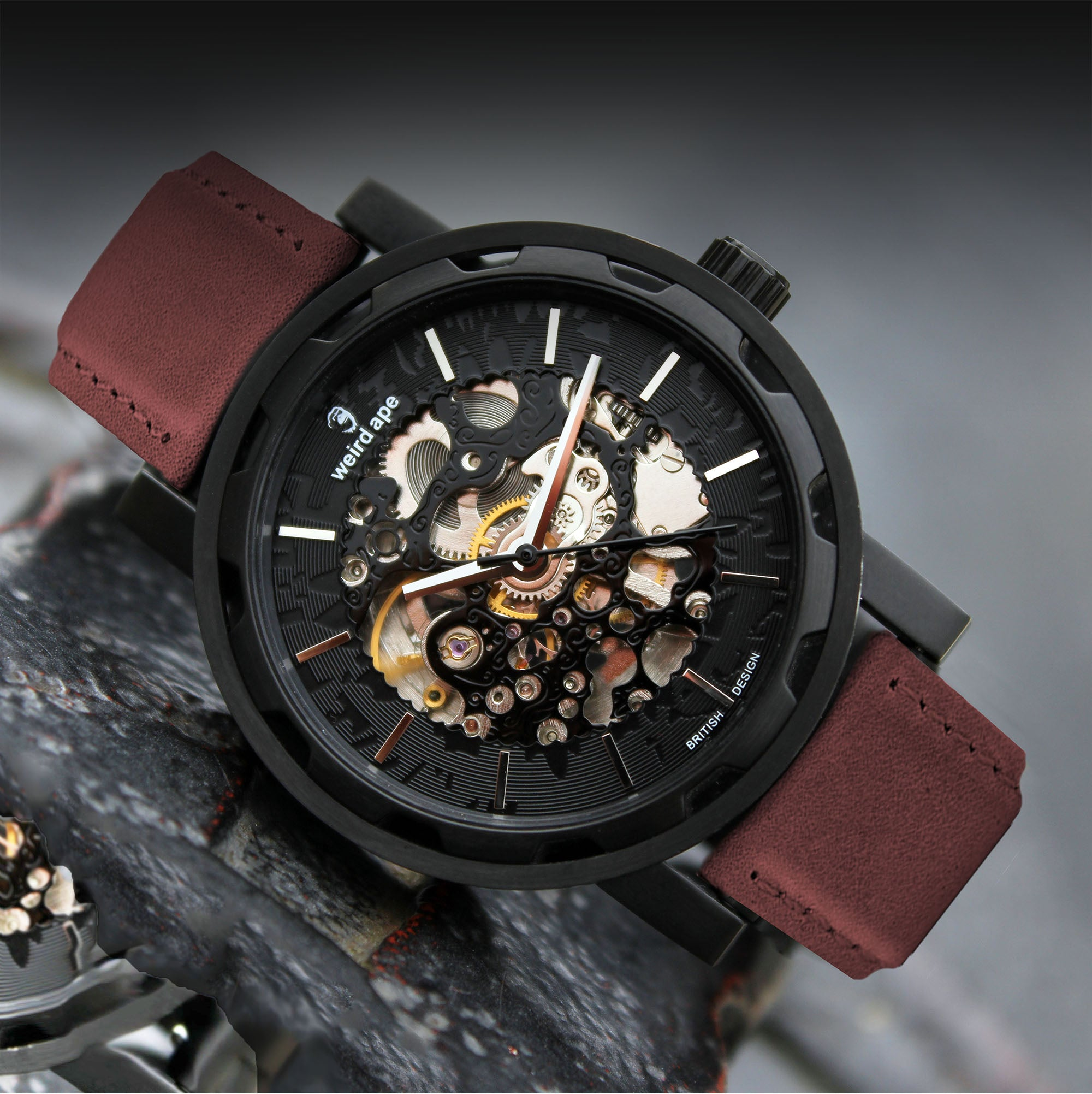 A picture of a black mechanical watch with a burgundy leather strap.