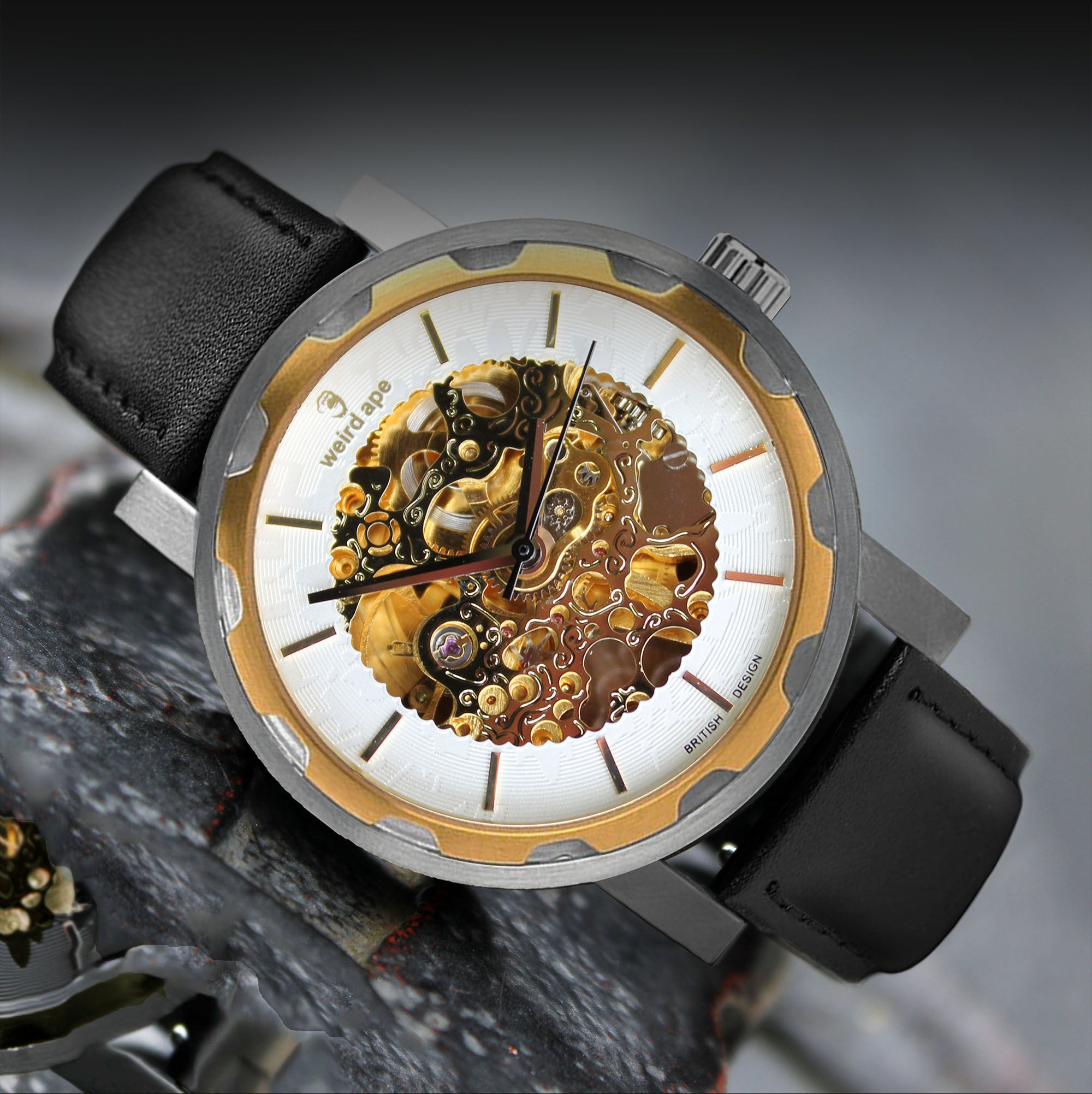 A picture of a gold mechanical watch with a black leather strap.