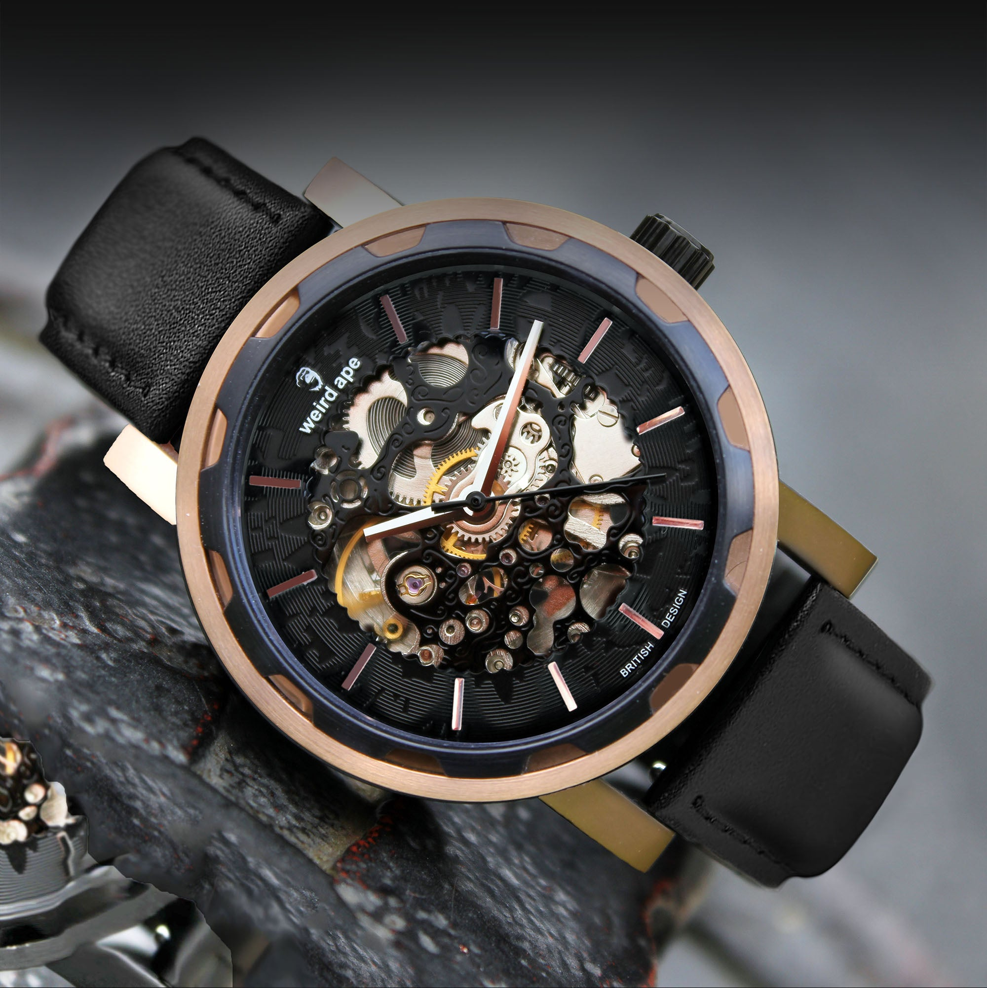 A picture of a rose gold mechanical watch with a black leather strap.