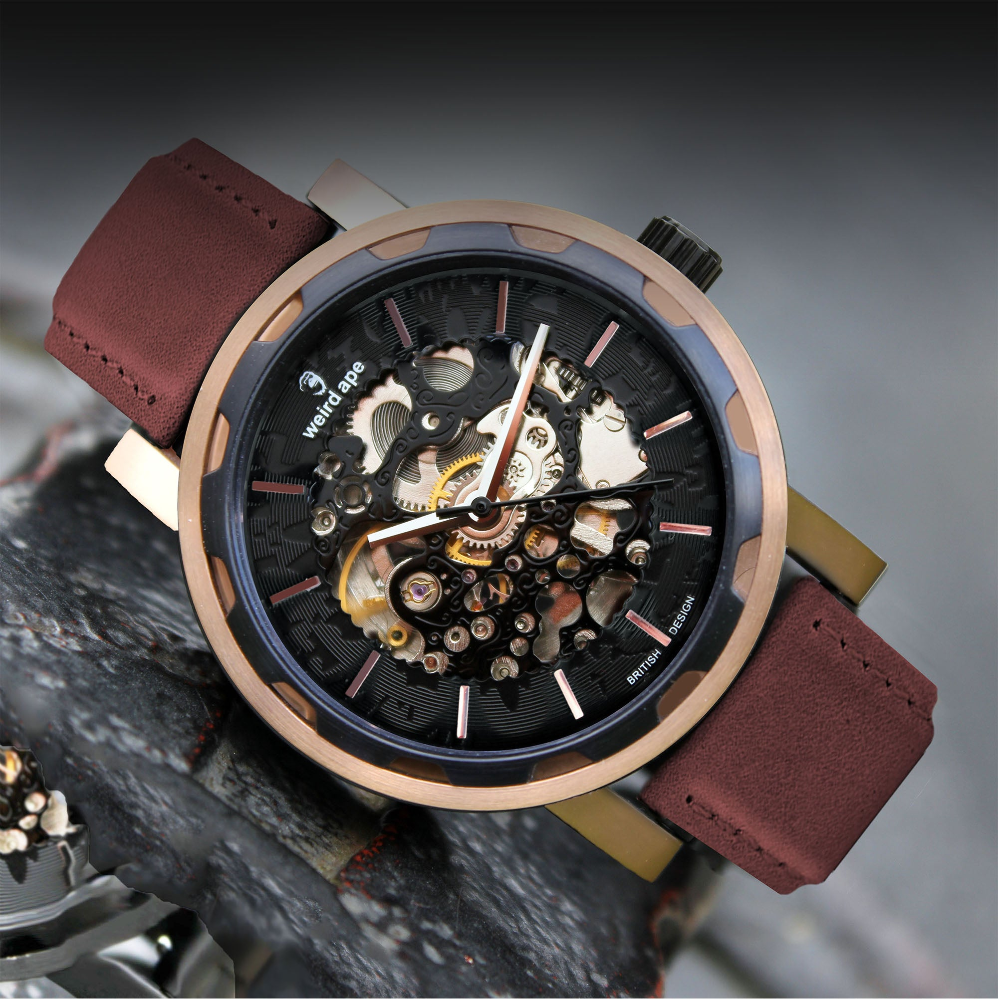 A picture of a rose gold mechanical watch with a burgundy leather strap.