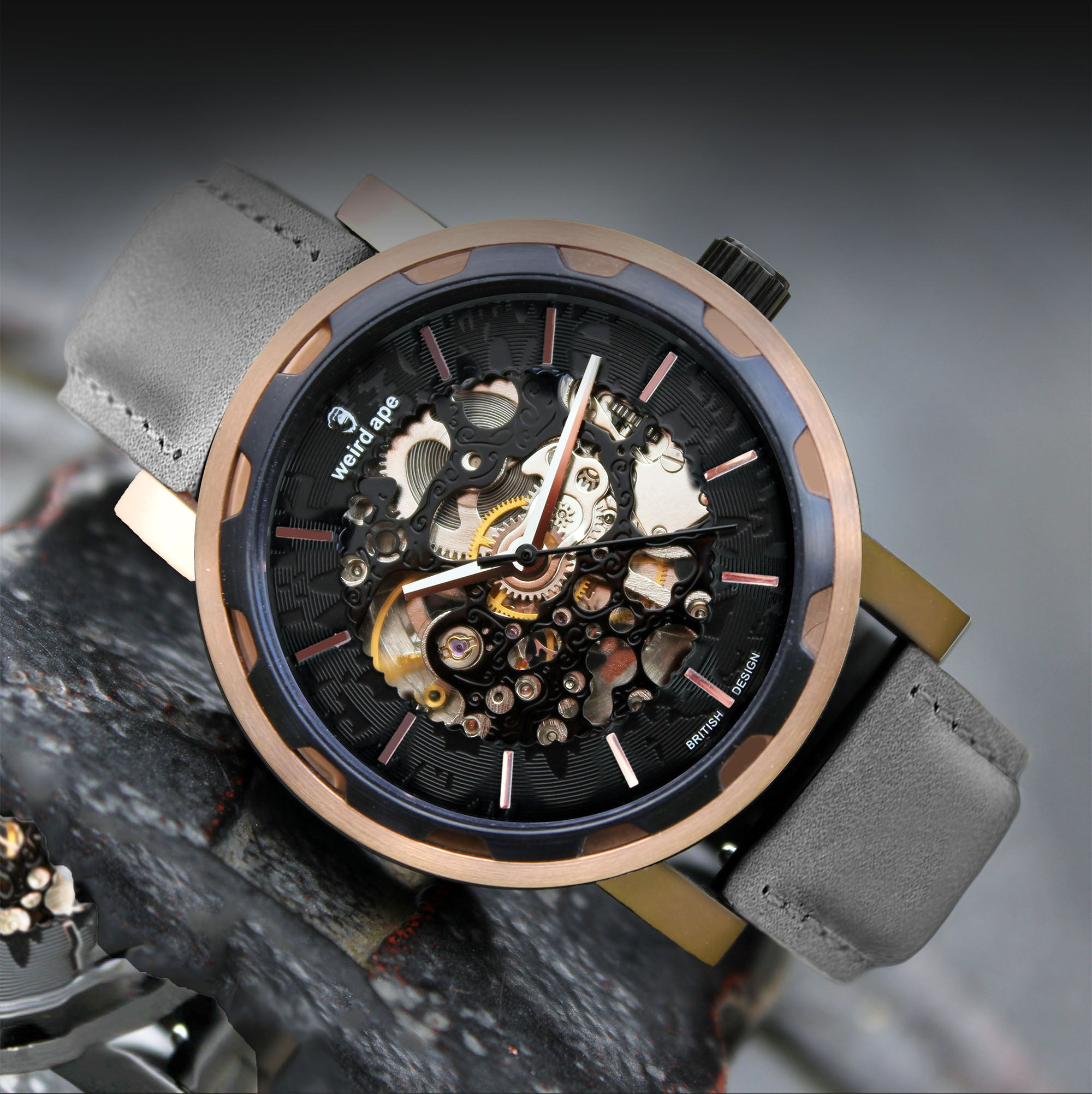 A picture of a rose gold mechanical watch with a leather grey strap.