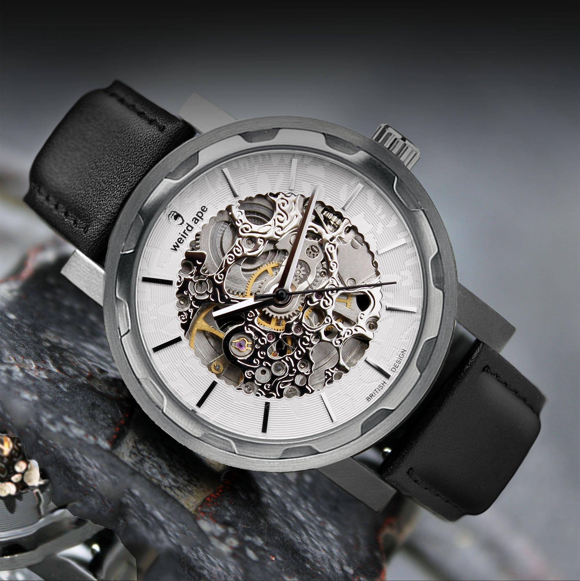 A picture of a silver mechanical watch with a leather black strap.
