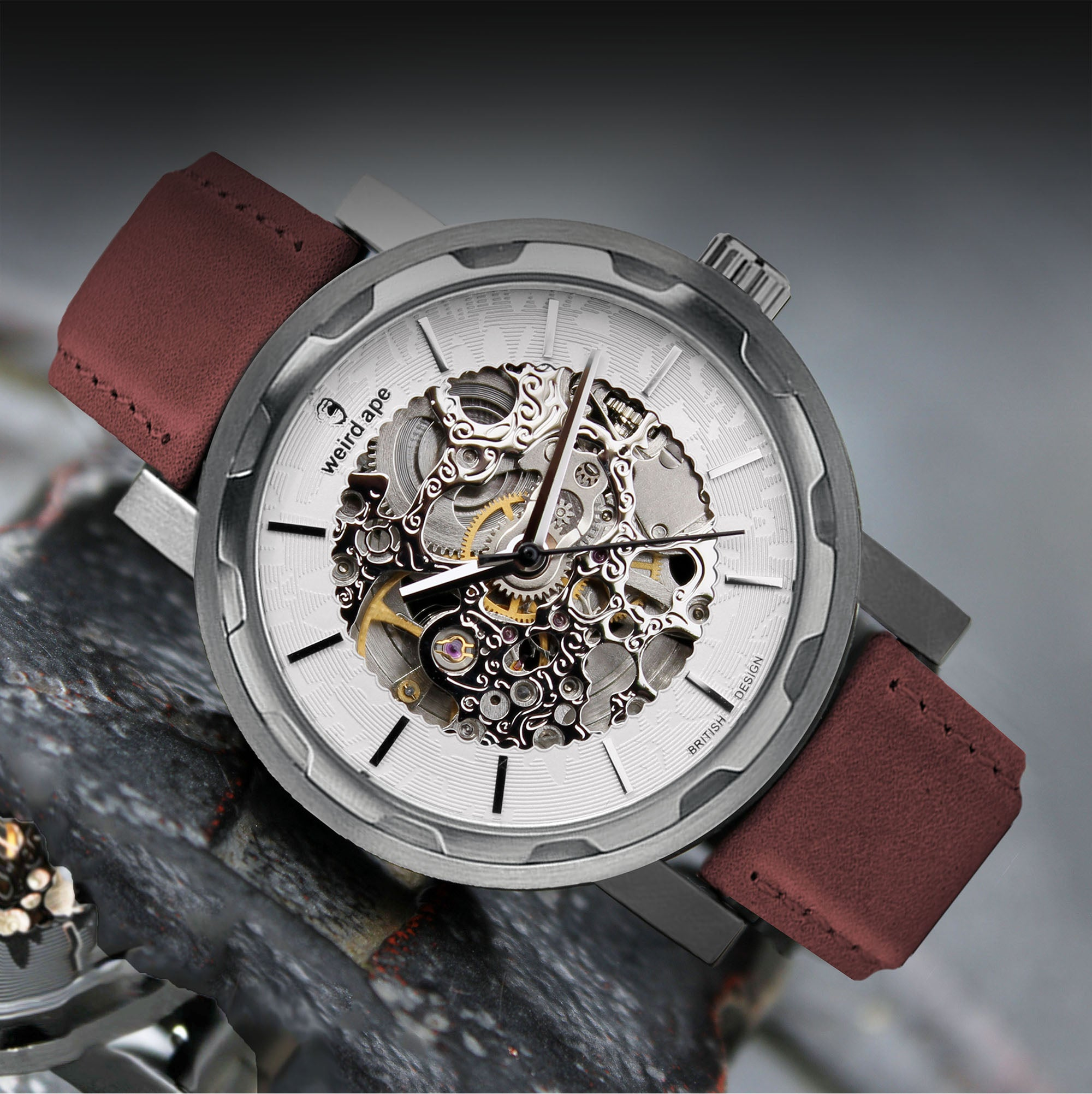 A picture of a silver mechanical watch with a suede leather burgundy strap.