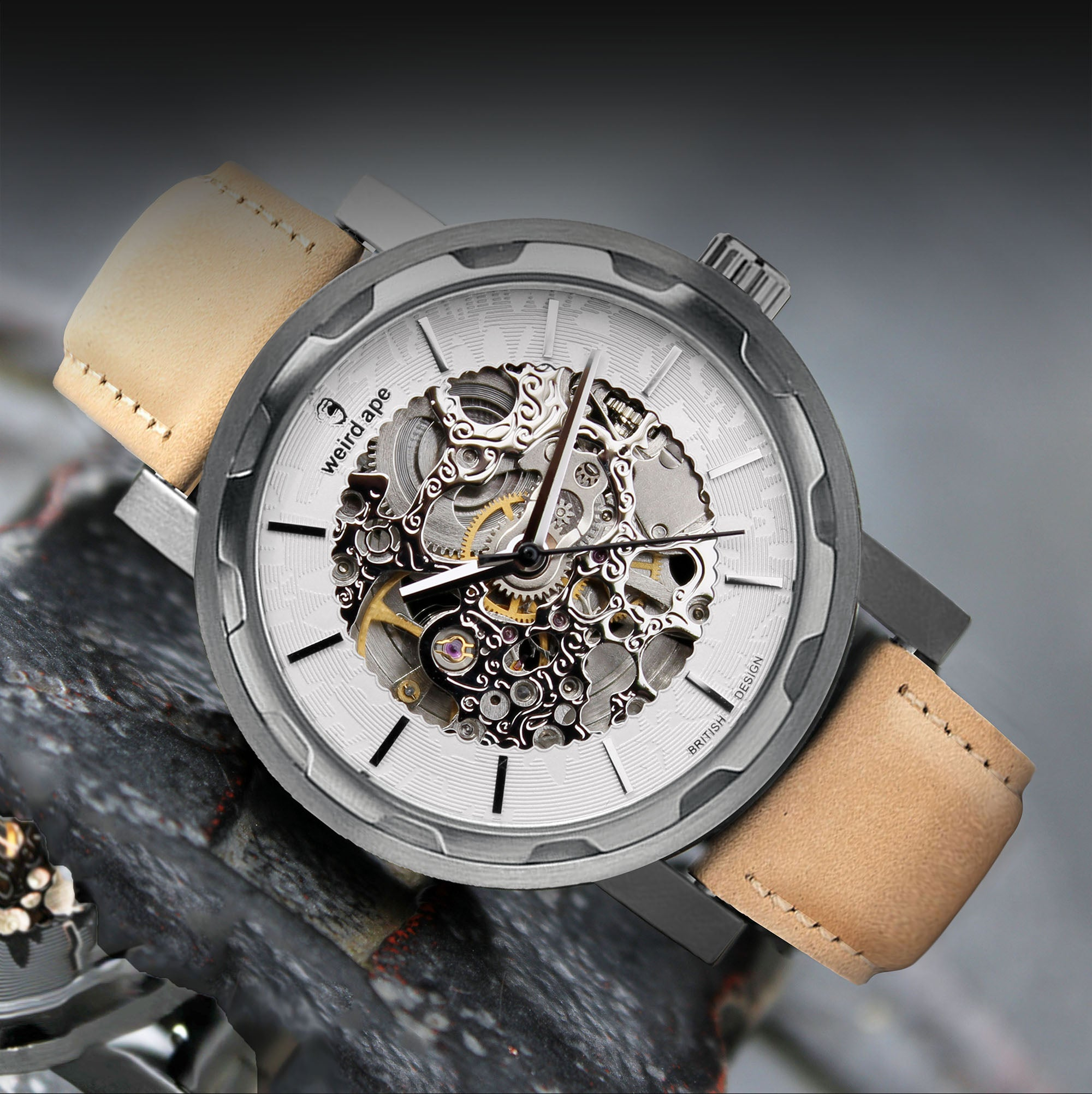 A picture of a silver mechanical watch with a suede leather sandstone strap.