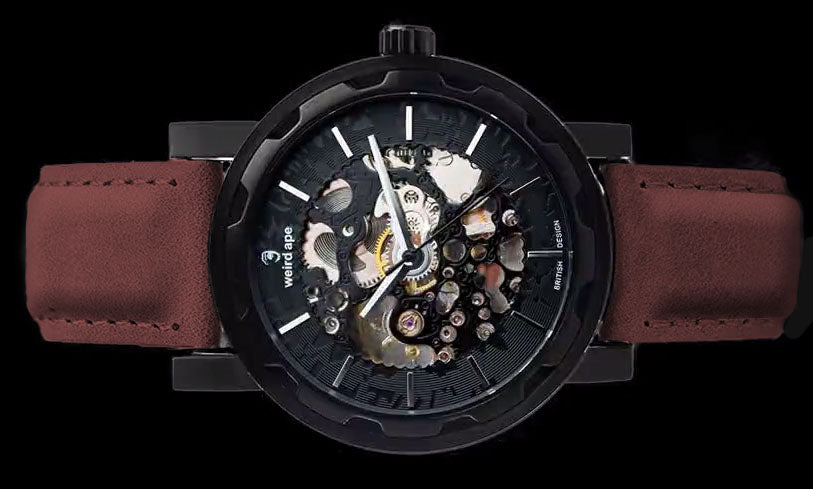 Black mechanical watch with burgundy strap on its side.