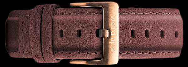 A burgundy suede leather strap with rose gold buckle for a mechanical watch.