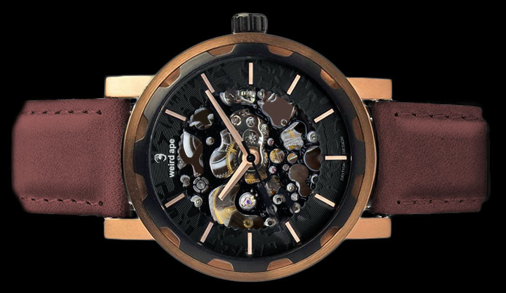 Rose gold mechanical watch with burgundy strap on its side.