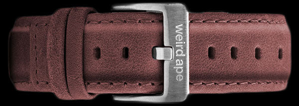 A burgundy suede leather strap with silver buckle for a mechanical watch.