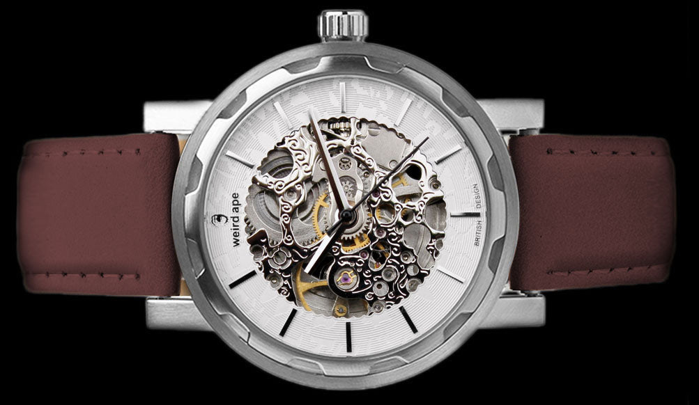 Silver mechanical watch with burgundy strap on its side.