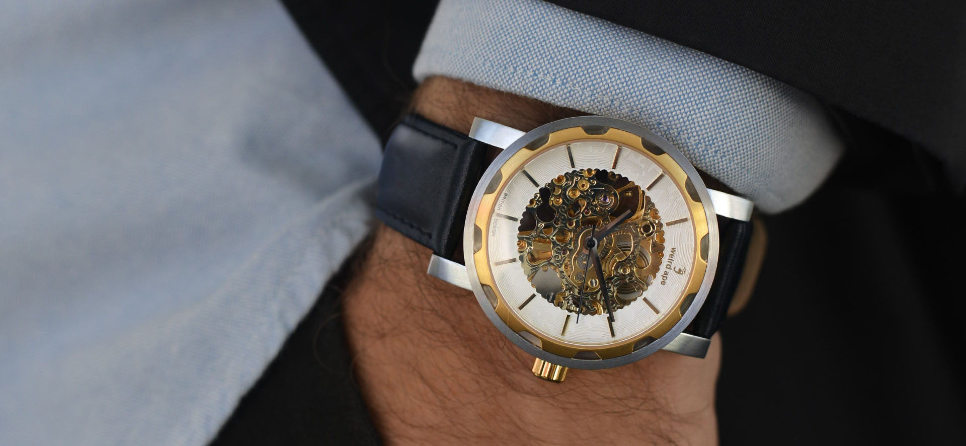 Gold skeleton watch with a black strap in a lifestyle image