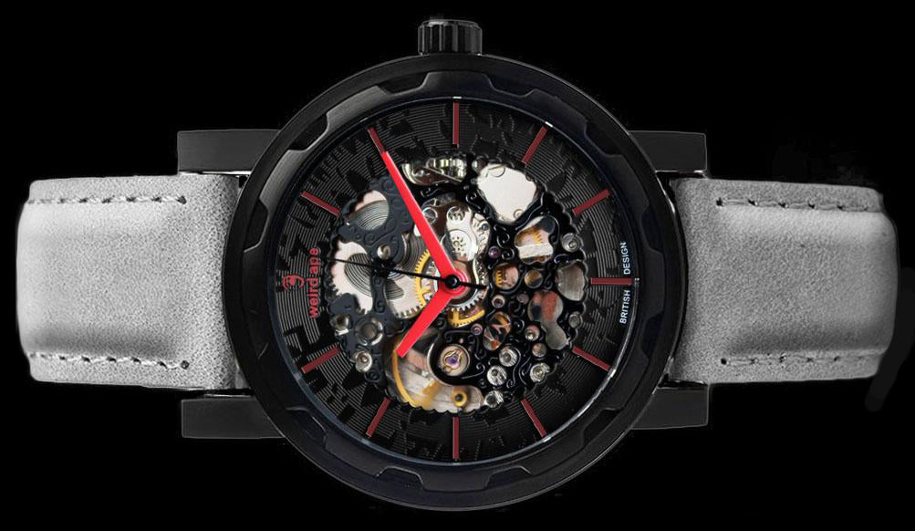 Black mechanical watch with grey leather strap on its side.
