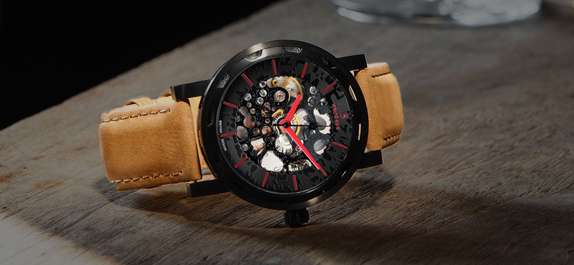Black skeleton watch with a tan strap in a lifestyle image