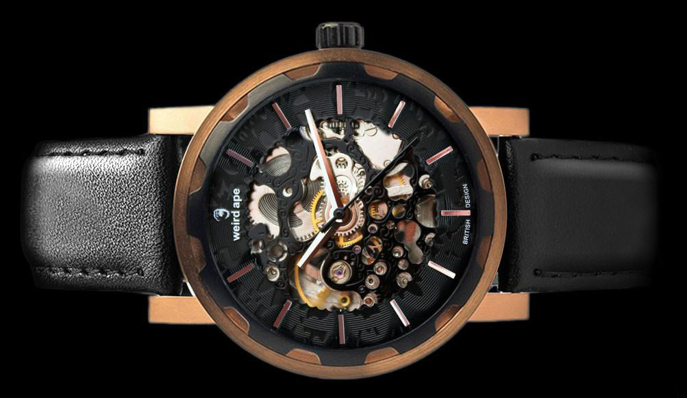 Black rose gold mechanical watch with black leather strap on its side.