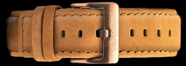A tan suede leather strap for a mechanical watch.