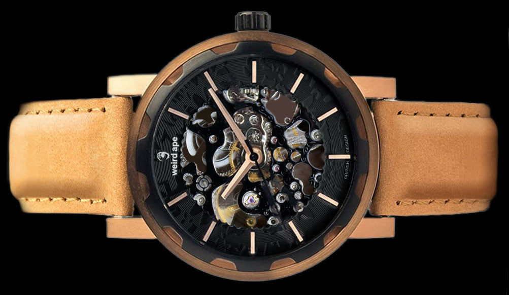 Rose gold mechanical watch with tan strap on its side.