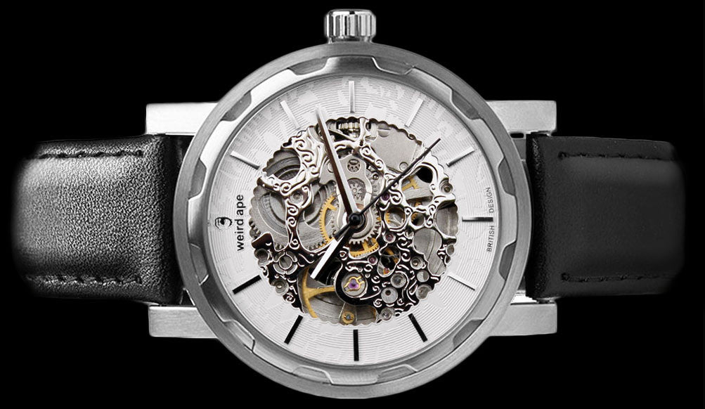 Silver mechanical watch with black strap on its side.
