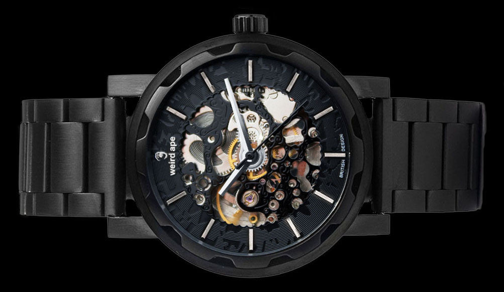 Black mechanical watch with black strap on its side.