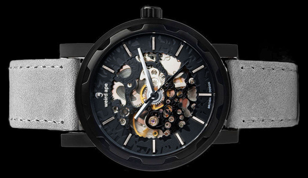 Black mechanical watch with grey strap on its side.