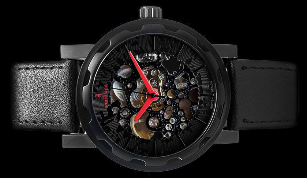 Black mechanical watch with black leather strap on its side.