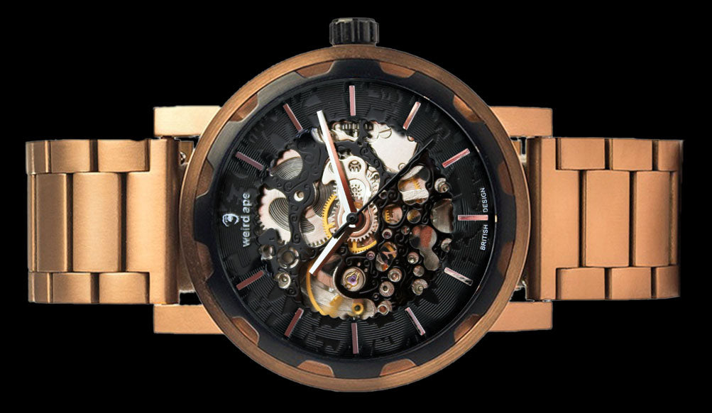 Black rose gold mechanical watch with rose gold strap on its side.