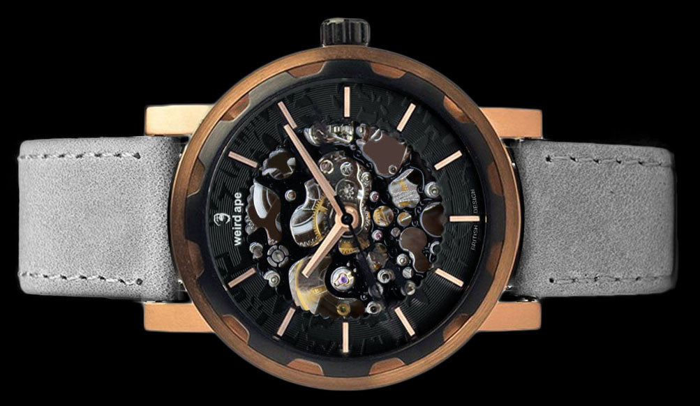 Rose gold mechanical watch with grey strap on its side.