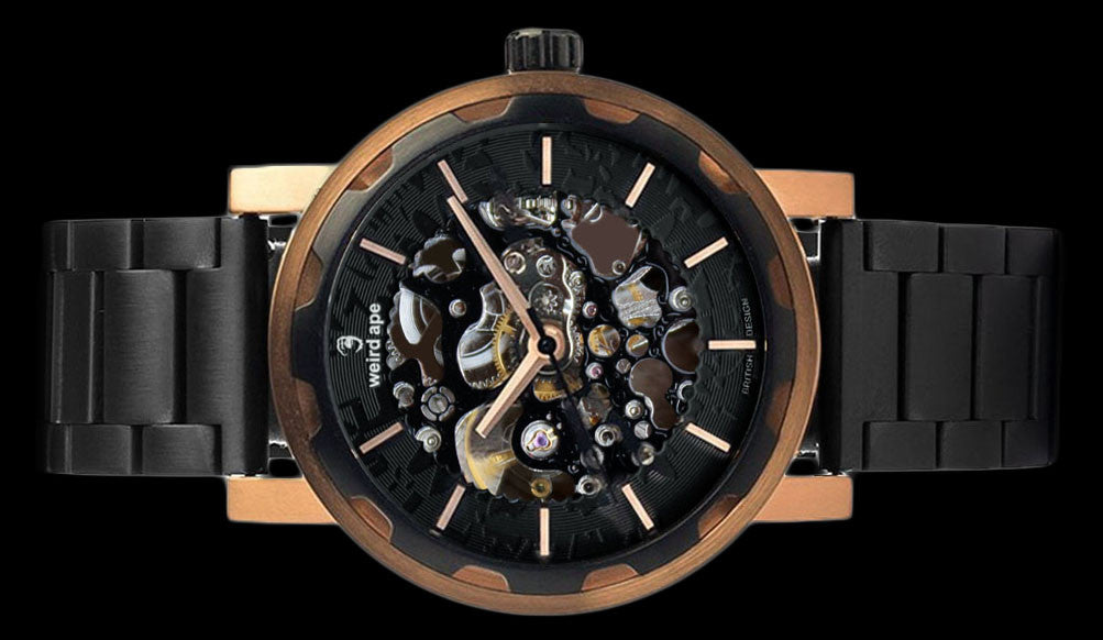 Rose gold mechanical watch with metal strap on its side.