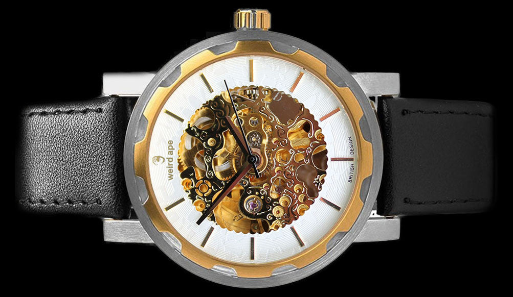 Gold mechanical watch with black strap on its side.