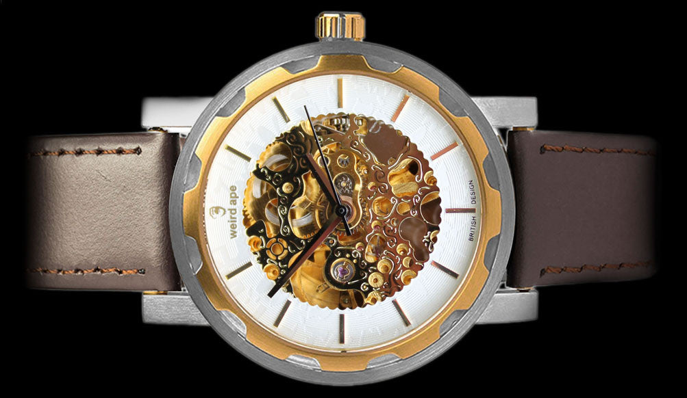 Gold mechanical watch with brown leather strap on its side.