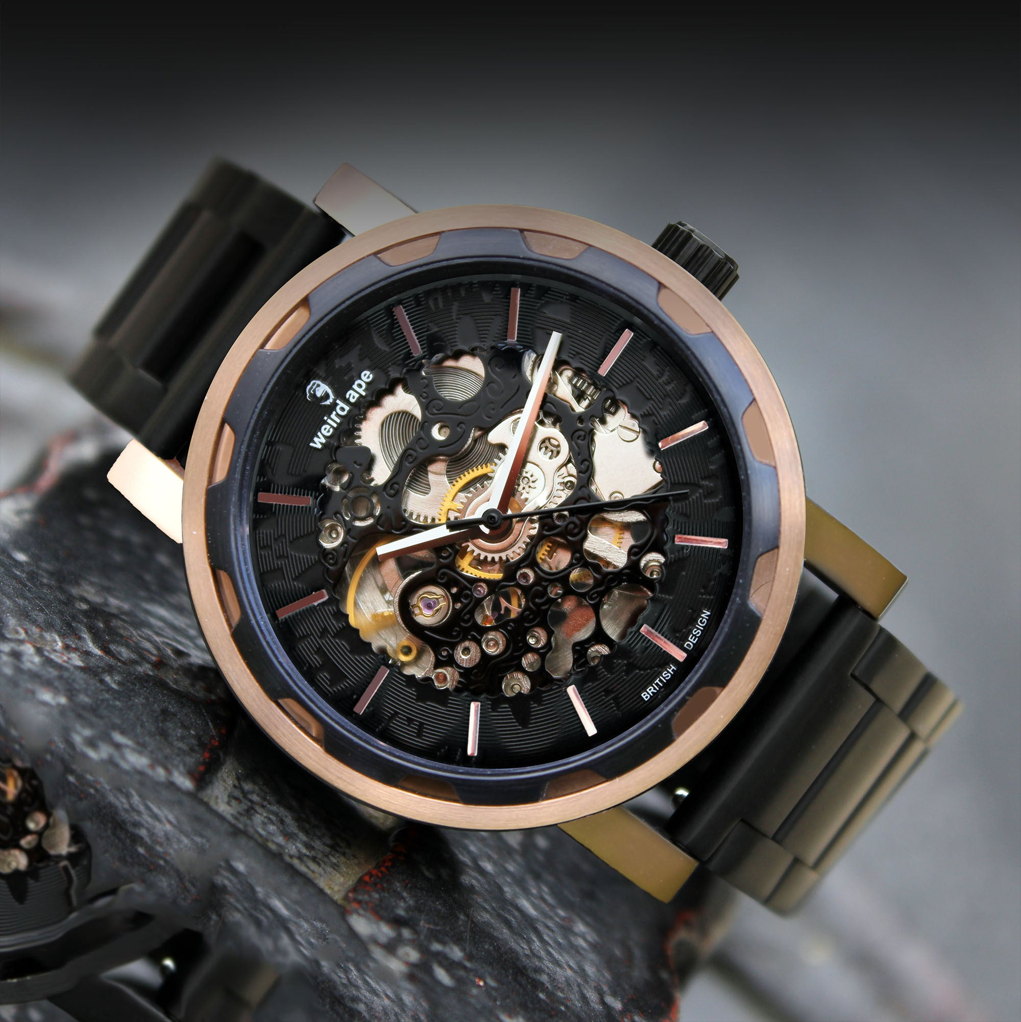 A picture of a rose gold mechanical watch with a black metal strap.