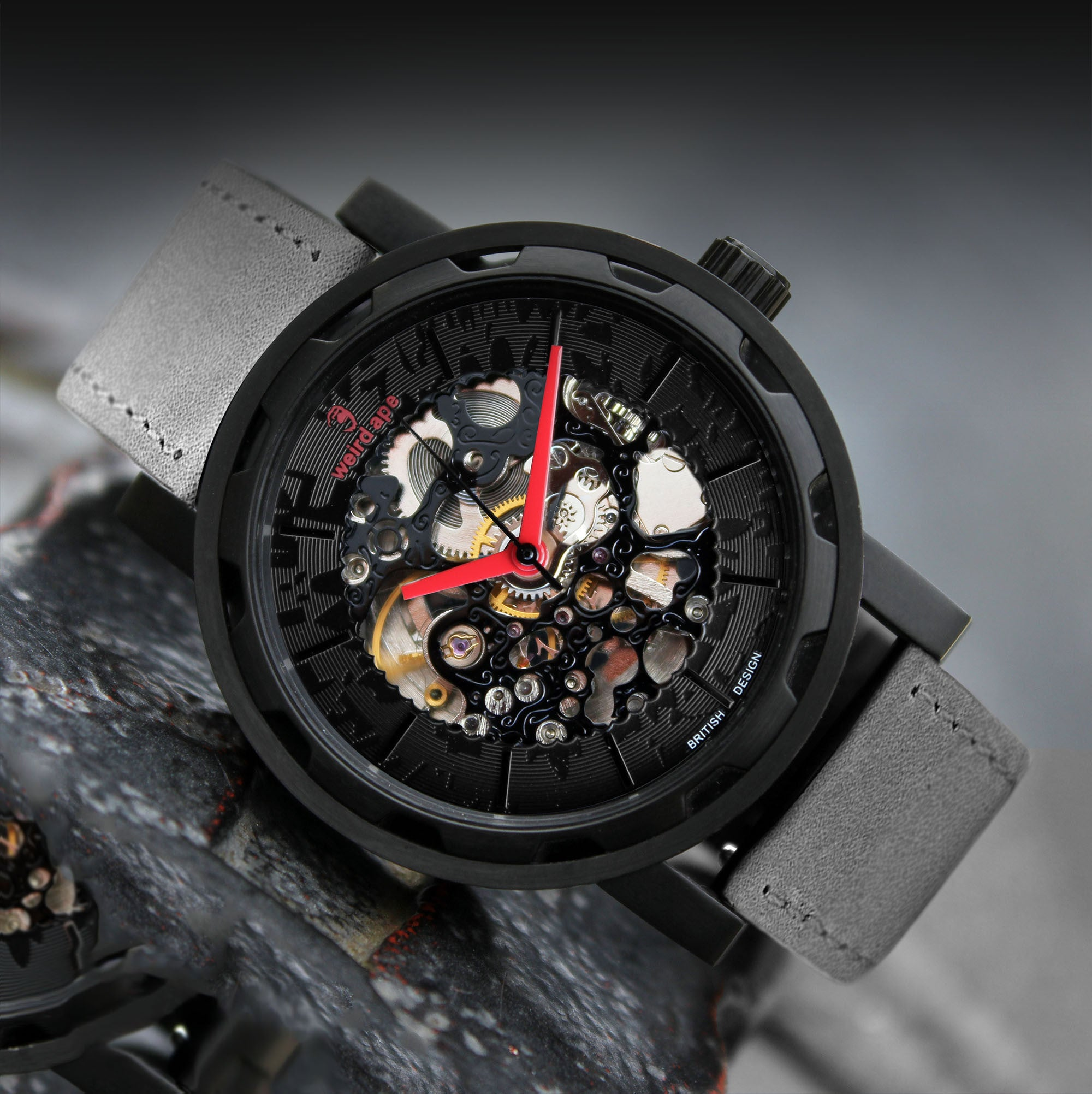 A picture of a black mechanical watch with red hands and a grey suede strap.